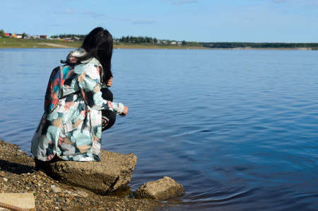 Modern sad girl Yakut looks at the village near the river vilyu contaminated with waste from diamond production in the North of Russia in Yakutia in the village of Suntar. Imagens