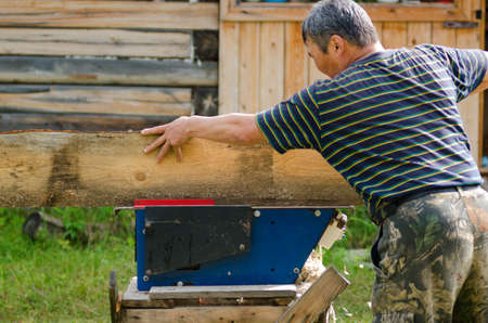 Adult Yakut man saws a Board on a saw against a house of timber in the Yakut village. Stok Fotoğraf