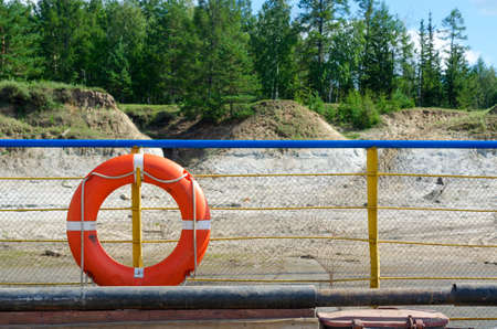 Orange life preserver attached to the deck railing of the ferry on the North river Vilyui amid the wild shores of spruce forest.