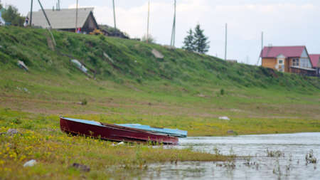 Old metal boat stands on land in the grass on the shore of the village houses of Northern Yakutia Suntar.