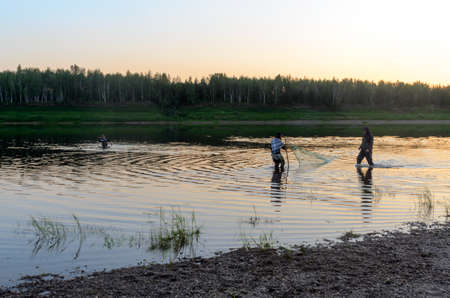 Two men Yakuts and graceful girl in a shawl to go in wading boots with fish net on the wildlife in the river Vilyuy in a forest traditionally catching local fish tugunok. Imagens