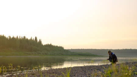 Young man Yakut squatting talking on a mobile phone on the banks of the wild Northern river vilyu in the taiga. 스톡 콘텐츠
