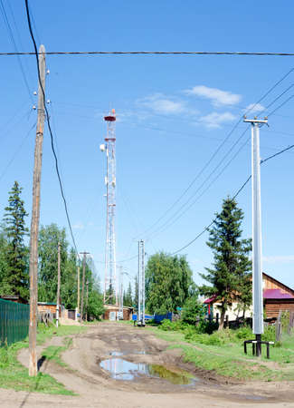 Power lines on concrete poles protected from impact by a car from below stand on a village street next to a puddle in the Northern Yakut village of Suntar.