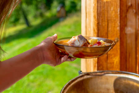Hands girl cooks outdoors hold a plate of soup borscht with meat and vegetables on the background of the boiler with food in nature.