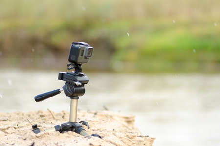 Action camera stands on a small tripod, recording video, on the sandy Bank of the river with grass and rain.
