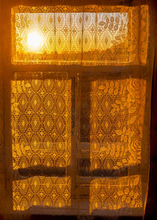 The bright yellow sunlight from the sunset over the horizon comes through a window in a rustic room with a white patterned curtain and a shadow frame. Foto de archivo