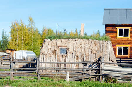 The room for cattle hoton, made of cow dung and wood, overgrown with grass stands on a modern plot with a house in the North of Yakutia. Editöryel