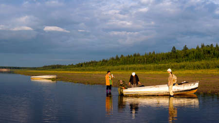 Three Yakut women and one Yakut man tinkering at a boat on the banks of the Northern Viluy river at sunset. Stockfoto