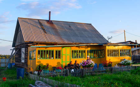 The yard of a private Yakut house with a fence near the forest and people sitting on the stairs among the flowers at sunset in the sunlight in the shade.