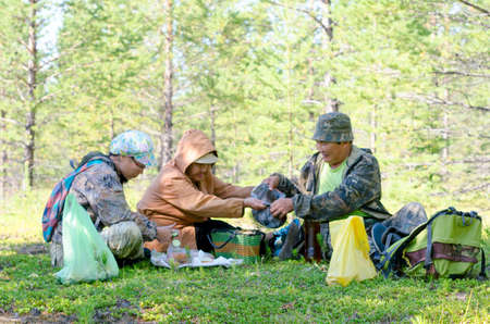A Yakut family on a picnic lays out food on the grass in a field near the Northern wild forest of the taiga in the afternoon in Yakutia. Stock Photo - 133840590