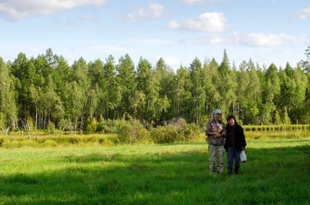 Yakut couple a young girl taller than an adult posing in a green field near the forest.