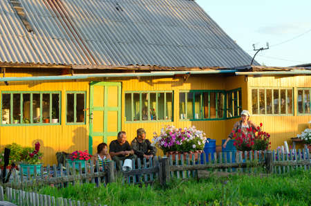 Group a family of two elderly men with a woman and one young girl sitting at sunset at the house in the shade next to flower pots and a fence with a vegetable garden.