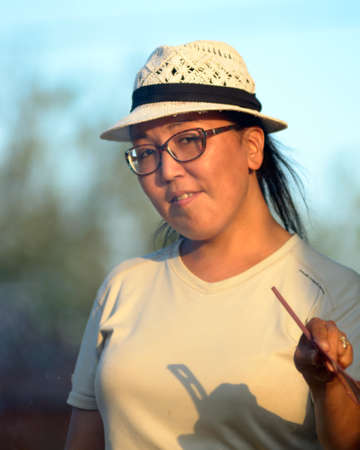 Yakut Asian girl in glasses and hat waving her fan in the rays of the setting sun smiling. Stock Photo