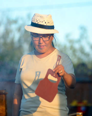Yakut Asian girl in glasses and hat waving a fire fan in the grill in the rays of the setting sun.