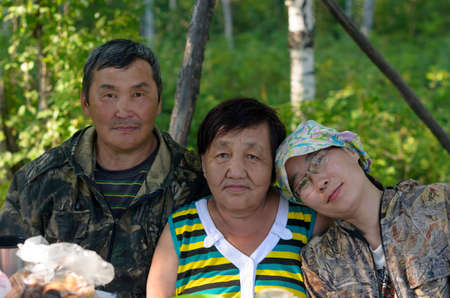 Family portrait of two elderly and one young daughter Yakut Asians in the Northern forest at the table.