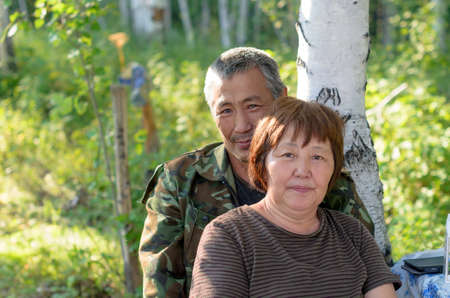 Portrait of an elderly Yakut Asian couple sitting in the woods near the birch.