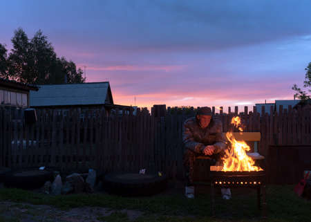 An old man sits alone on a bench in the village plot behind the fence at the house looking at the fire in the grill in the evening at sunset.