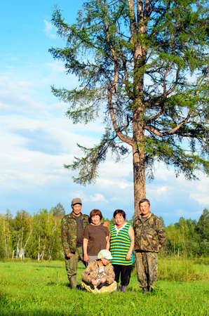 Two Yakut Asian elderly couples men and women with a young girl sitting on the grass pose for a family photo in a field near a large lonely tree.