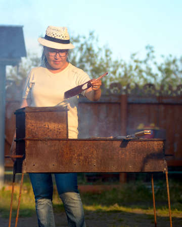 Yakut Asian girl in glasses and hat waving a fire fan in the grill with cooking meat in the rays of the setting sun. 写真素材