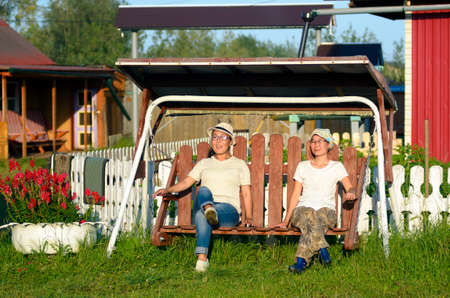 Two girls Yakut friends relax on a wooden swing next to flowers on a residential plot in a village in the North of Yakutia enjoying the warm sunlight at sunset in the evening.