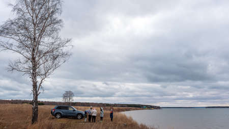 Novosibirsk, Russia-October 29, 2018 Suzuki Escudo car stands on a yellow grass field with vacationers in autumn under a big birch by the sea in Novosibirsk on October 29, 2018.
