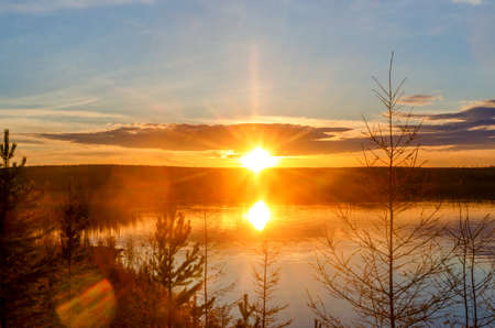 Bright colorful sunset with a sunbeam on the Vilyuy river in the Northern taiga of Yakutia Suntar against the background of fir trees on the shore under a cloudy sky.