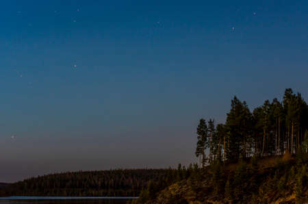 Night landscape of the steep Bank of the taiga of Yakutia next to the calm water of the vilyu river. 写真素材
