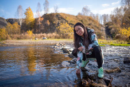 Yakut Asian girl in glasses posing smiling sitting by the water and touching the surface.