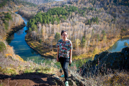 Yakut Asian girl in glasses in a t-shirt and with a handbag posing smiling standing at the side of the mountain with a river turn at the bottom of the Berd rocks.