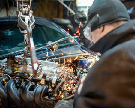 A bespectacled car mechanic in the garage works with sparks flying from under the saw setting the engine in the car.