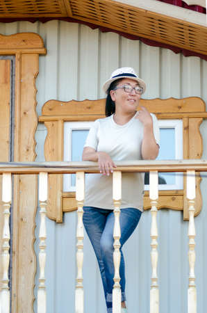 Yakut girl in jeans and glasses posing on a wooden balcony at the village house Zha window leaning on the railing. 写真素材
