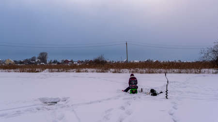 A girl fisherman in winter clothes sits on a box on the ice with snow next to an ice breaker on the lake against the evening sky and the houses of the village on the horizon.