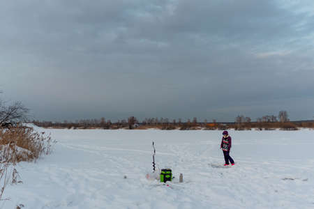Girl angler in winter clothes walking with a fishing rod at the box on the ice with snow next to the ice breaker on the lake against the background of the evening sky and trees on the horizon.