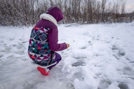 Girl angler in winter clothes sitting on one leg fishing in the snow in a hole with ice on a small fishing rod. 写真素材