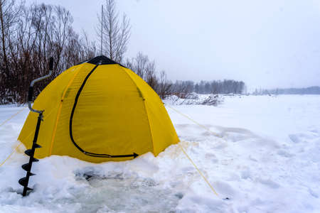 A winter yellow fishing tent stands next to an ice pack on snow and ice in a Blizzard on the lake near the trees.