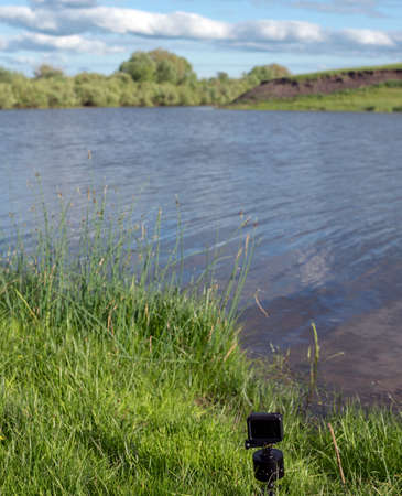 Action camera stands on a panoramic tripod head on the river Bank in the green grass. 写真素材