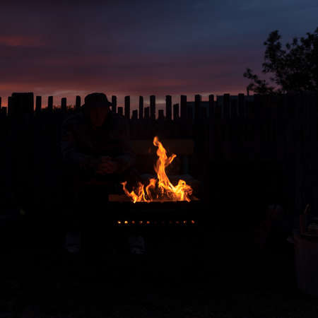A man in the shade looks at the flames of the fire in the grill at night against the background of the setting sun at sunset in the village behind the fence.