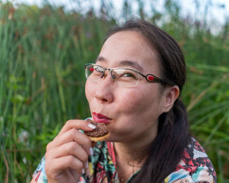Smiling Asian Yakut girl with glasses, sitting in the grass eating cookies with flying crumbs.
