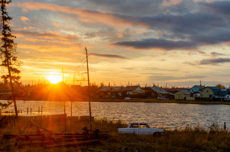 Bright colorful sunset in the village of Yakutia Suntar on the background of the silhouette of an old car at the lake with houses on the shore under a cloudy sky.