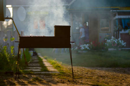 Iron grill with barbecue smokes in the rays of the setting sun on the background of a private house and bustling women in the distance at the door with flowers in Yakutia. 写真素材