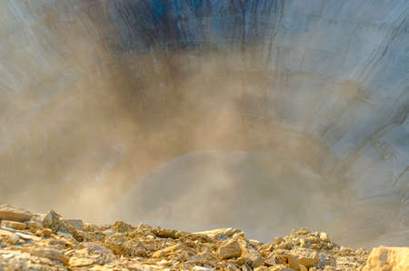 The cut in the ground-closed Yakut quarry Mirny for diamond mining filled with water with a mist of dust that is lifted to the top among the stones. 写真素材