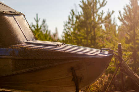 The bow of an old iron boat stands on a trailer in the early morning in the taiga in the rays of the rising sun. 写真素材