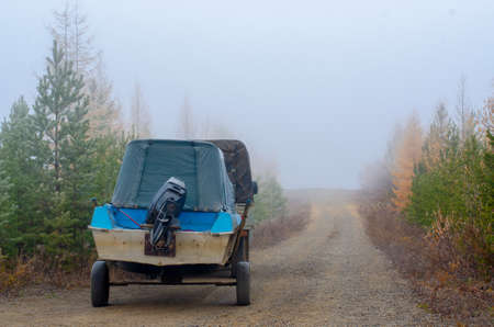A boat on a trailer with a motor is on the road in the spruce taiga in the morning fog with yellow and green coniferous trees in the tundra of Northern Yakutia.
