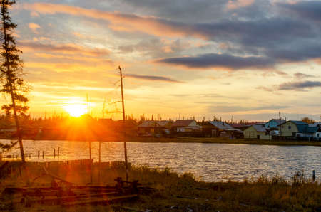 Bright colorful sunset in the village of Yakutia Suntar on the background of old fir trees by the lake with houses on the shore under a cloudy sky.