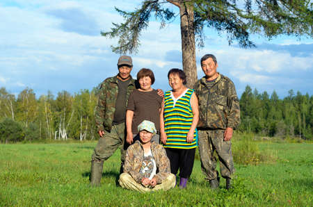 Two Yakut Asian elderly couples men and women with a young girl sitting on the grass pose for a family photo in a field near a tree.