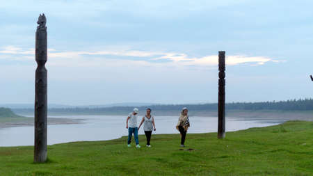 Three Yakut girl friends, one wrapped in a blanket, walk away from the river past the ritual national pillars of Serge at sunset in the evening in the wild North of Yakutia. 写真素材