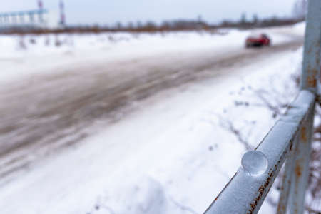 A small glass ball lies in winter on the railing in the snow on the background of a dirty road with a car leaving.