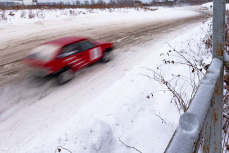 A small glass ball lies quietly in winter on the railing in the snow against the background of a turn on a muddy road and the silhouette of a racing car at high speed.