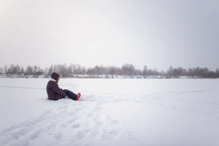 A lonely girl sits on the snow ice of a winter lake, clasping her knees with her hands. Banco de Imagens