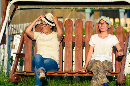 Two girls girlfriends Asian Yakuts relax on a swing next to flower beds on a residential plot in a village in the North of Yakutia enjoying the warm sunlight.